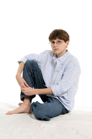 Cute boy with short hair and glasses, sitting with knee up and untucked shirt.