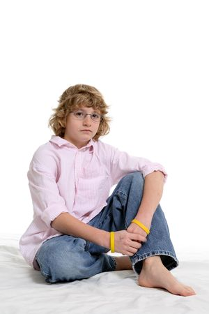 Cute boy with a pink button down shirt sitting against a white background.