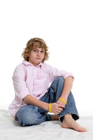 Cute muchacho con una rosa botón camisa sentado sobre un fondo blanco.  Foto de archivo - 3101723
