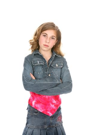 defiant: Young girl dressed in denim, standing with her arms crossed and a defiant look on her face. Stock Photo