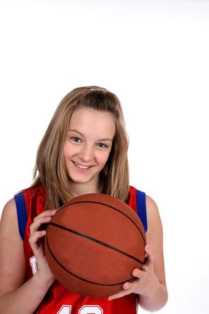 Caucasian teenage girl in a red jersey, holding a basketball against a high key background. Standard-Bild