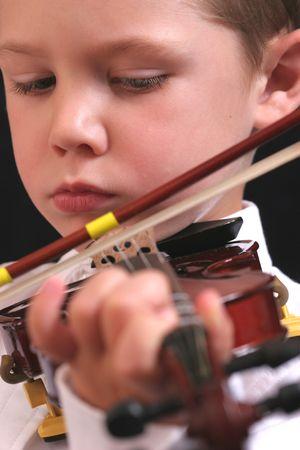かわいい少年がバイオリンを弾きます。 写真素材
