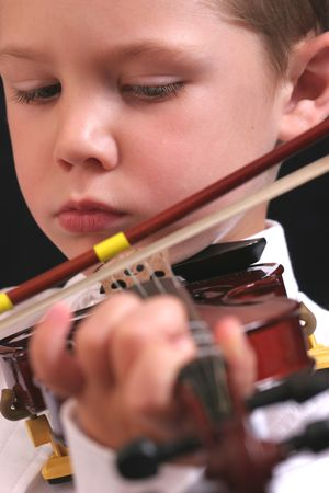 Cute young boy playing the violin.