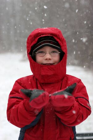 Young boy in glasses catching falling snow in his mittens. Stock Photo - 3150747