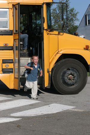 Happy boy with glasses getting off the yellow school bus after the first day of school. photo