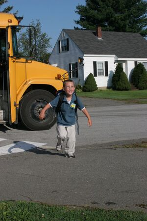 off day: Young boy running off the schoolbus after his first day of school.