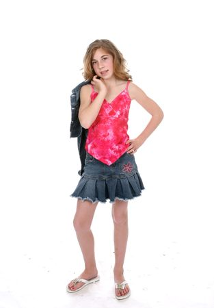 Full length picture of cute tween girl in stylish outfit against high key background.