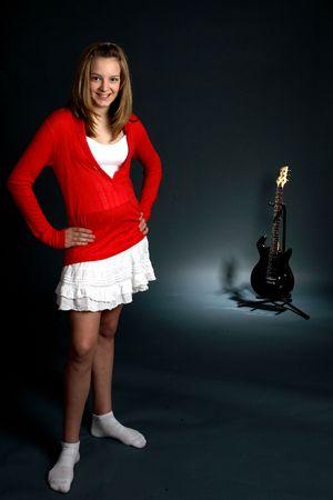 背面に黒のエレク トリック ギター、フォア グラウンドで十代の少女。
