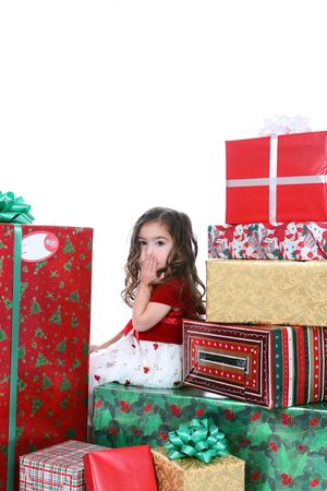 Little girl in holiday dress sitting in a huge pile of Christmas presents with her hand over her mouth. Stock Photo - 3150813