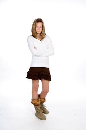 茶色のミニのスカートと背の高い、10 代の少女は、トップ上の毛皮のブーツをレースします。