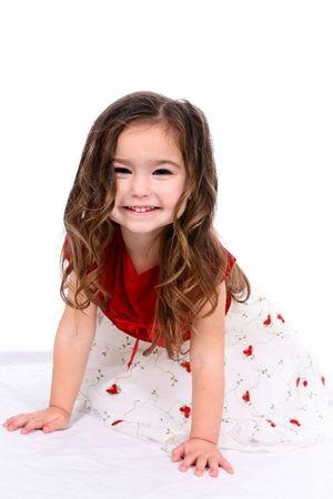 赤と白の休日を着て幸せで、美しい子供ドレスします。