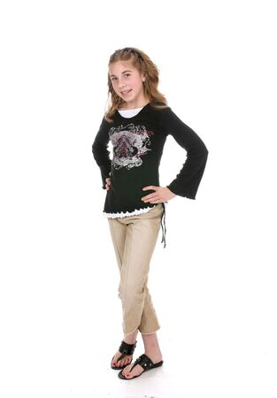 Pretty young girl standing with her hands on her hips and her legs crossed. Stock Photo - 3150730