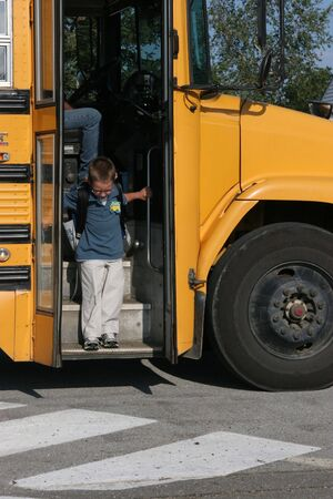 Young boy attempting to step off the big step of the yellow school bus.