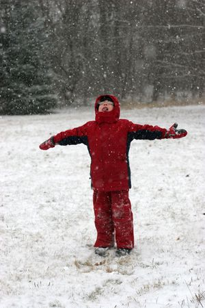 Small child with hands outstretched; catching and eating snow during a storm.