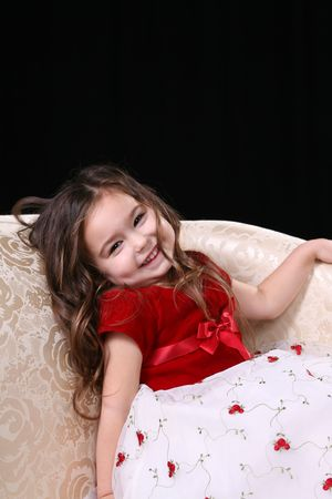 velvet dress: Pretty little girl in red and white dress on a couch.