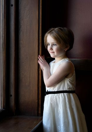 Pretty little girl looking out a large window and wearing a pretty dress. Reklamní fotografie