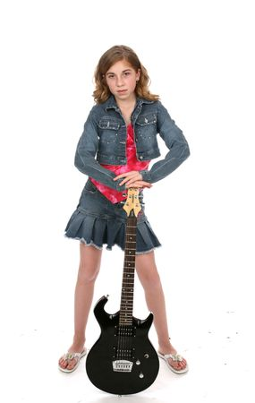 Cute girl wearing denim and leaning on a black electric guitar. Reklamní fotografie - 3160667