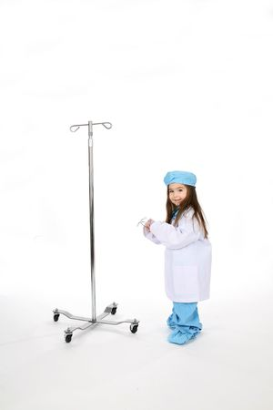Young child dressed in medical scrubs next to an IV stand and holding a stethescope. Stock Photo - 3160648