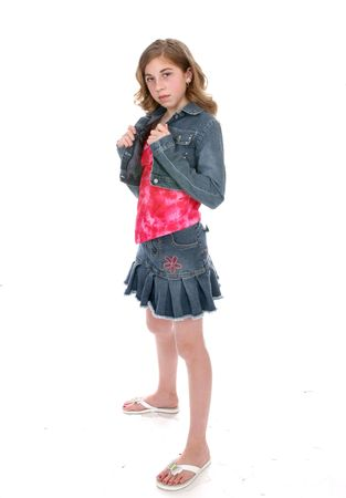 Defiant looking young girl wearing a short denim mini skirt and a cropped denim jacket. Stock Photo