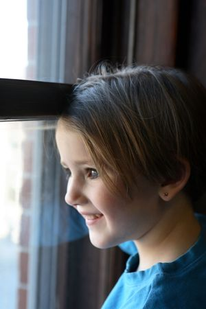Pretty little girl looking out a window.