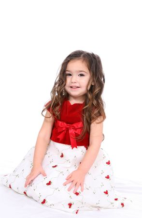 Pretty little girl in a red and white holiday dress, sitting against a white background. Stock Photo - 3160686