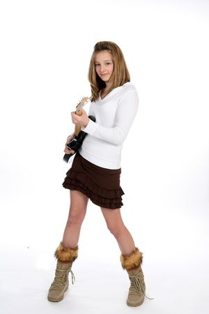 skirt up: Stylish teenage girl in mini skirt and tall boots playing an electric guitar. Stock Photo