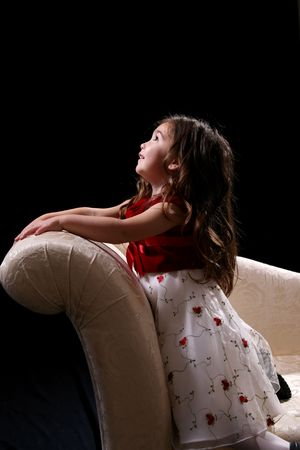 Pretty little girl kneeling on a couch and looking up.