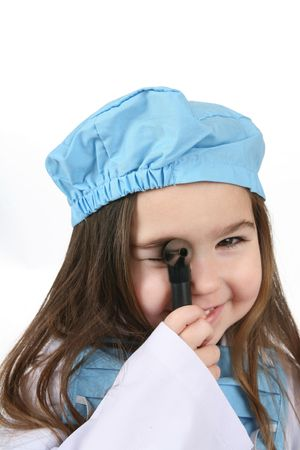 Toddler girl in blue medical scrubs looking through a medical instrument as if examining someone. photo
