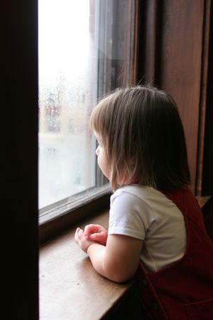 Little girl looking out the window at a rainy day outside.