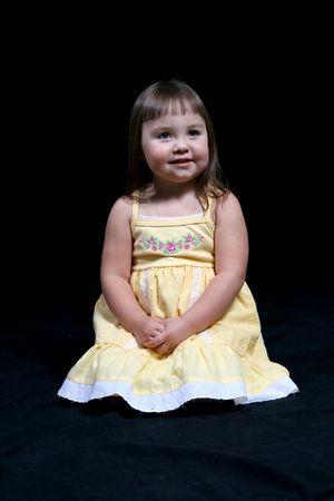 Pretty little girl in yellow sun dress against a dark background. Stock Photo - 3194830