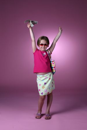cute young girl in  patterened clothing holding dollar bills up in the air