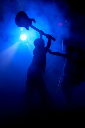 brother sister fight: Silhouette of big brother holding guitar up in the air and getting ready to smash it on his little sister, who has her hands out in defense; on stage with fog. Stock Photo