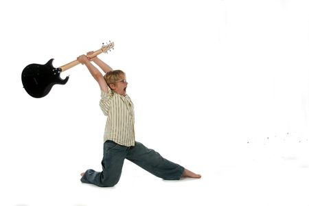 Young boy with black electric guitar raised up over his head as if he's going to smash it.