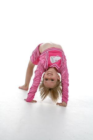 cute girl in a gymnastics bridge position and a pink cheering outfit Stock Photo