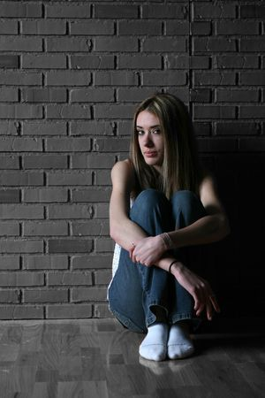 Tenage girl in color with her knees up and arms around them, sitting against a black and white brick wall and wood floor background. Stock Photo - 3209121