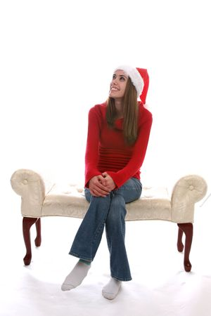 Pretty teenage girl sitting on a bench with her legs crossed and wearing a Santa Hat. Stock Photo - 3209106