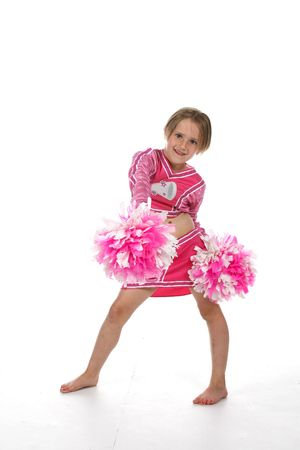 cute little girl in pink cheering outfit and pom poms photo