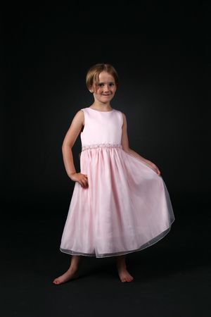 pretty girl holding the skirt of her long pink dress photo