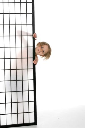 pretty girl peeking out from behind a screen with just her head and fingers showing. photo