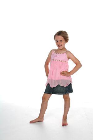 schattig meisje in het roze shirt en denim rok met haar handen op haar heupen.