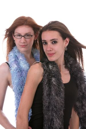 two beautiful teenage girls with windblown hair and fluffy scarfs photo
