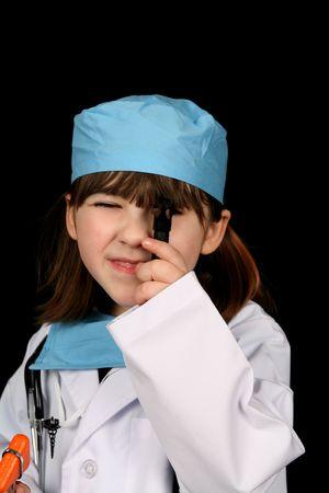 Little girl looking through medical instrument, wearing scrubs photo
