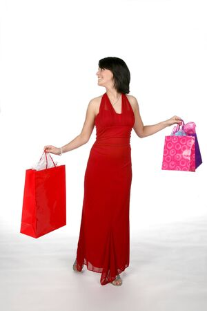 pretty teen wearing a red gown and carrying shopping bags Stock Photo