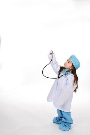 little girl in medical scrubs holding up stethoscope Stock Photo - 3282166