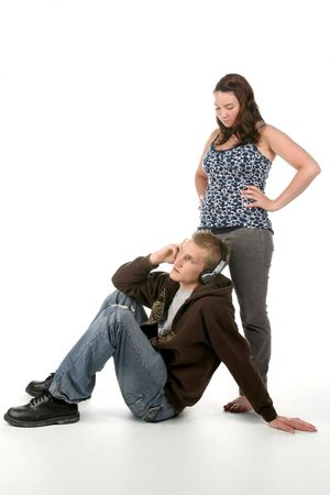 copule: grunge style man on floor listening to headphones with woman standing next to him