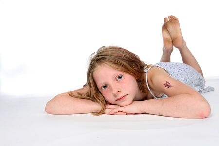 thoughtful girl on stomach with a temporary tattoo on arm