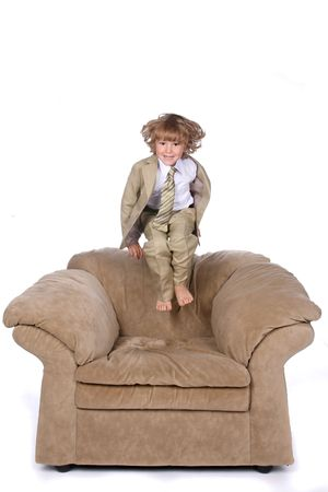 boy in suit jumping on chair Stock Photo