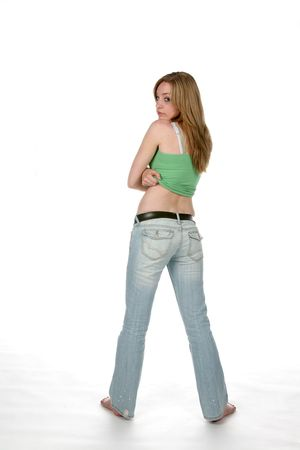back straight: woman lifting shirt from behind and turning to look at camera Stock Photo