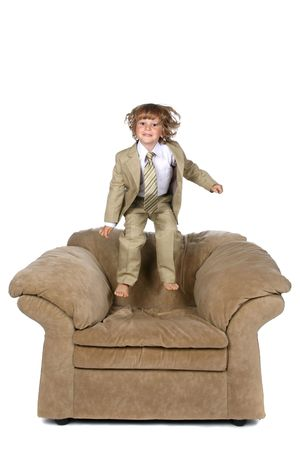 cute boy in suit jumping on big chair Stock Photo