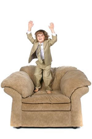 boy jumping on chair Stock Photo